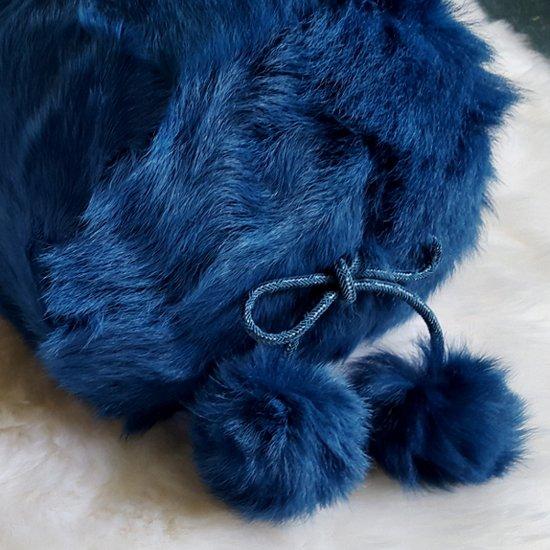 Electric blue kid skin bolster cushion with pom poms. 600x600px